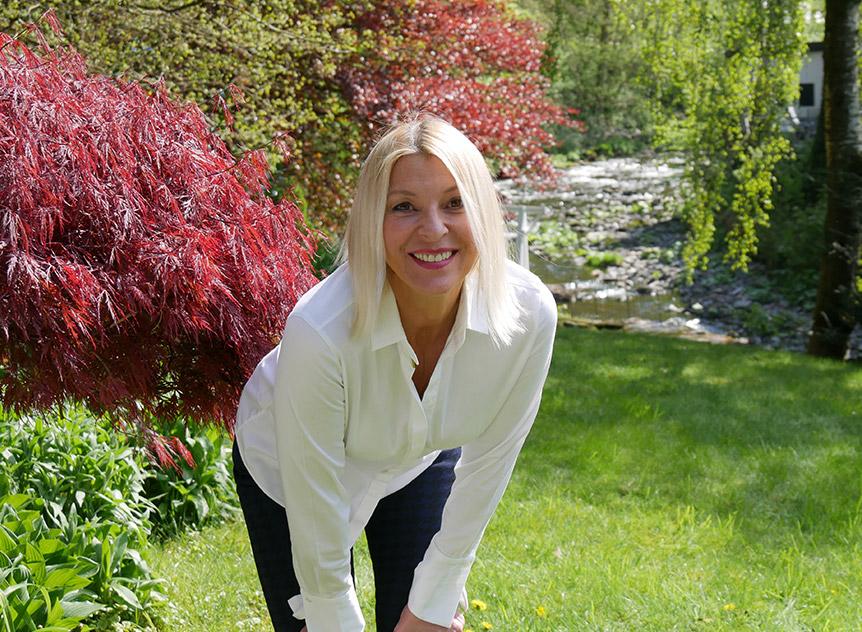 Gisela Hoock von 321Health.de steht im Garten und lacht in die Kamera